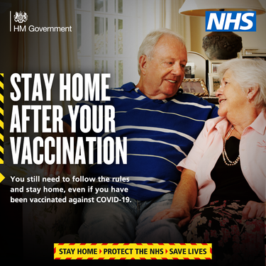 stay home after your vaccination.  Image of a couple on a sofa