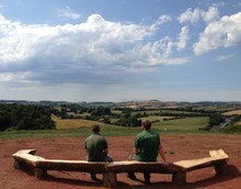 Two guys sitting on a wooden bench looking out into open green space