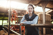 woman leaning on bars on farm