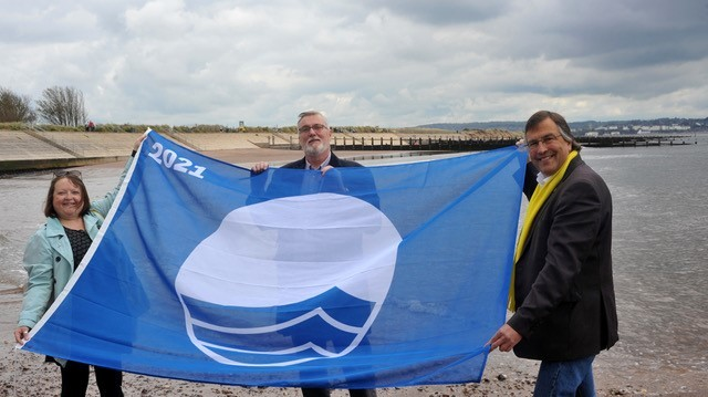 Cllrs Linda Goodman-Bradbury, Andrew McGregor and Martin Wrigley hold up the blue flag awarded to Dawlish Warren beach