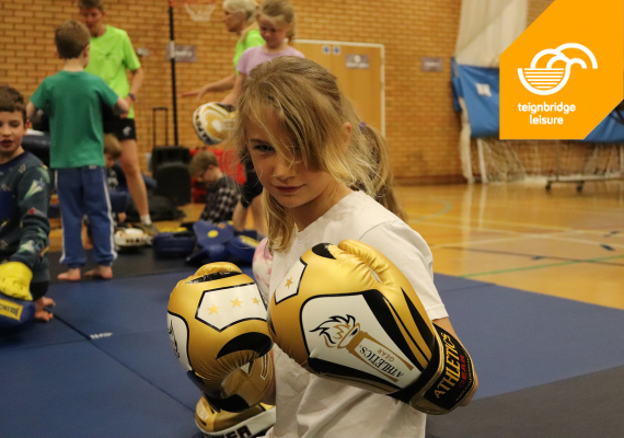 Young girl with boxing gloves in leisure centre