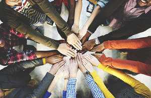 Overhead shot of diffrent people holding arms to the centre with hands touching