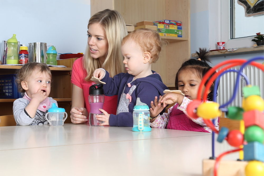 Child carer and children playing activities in classroom