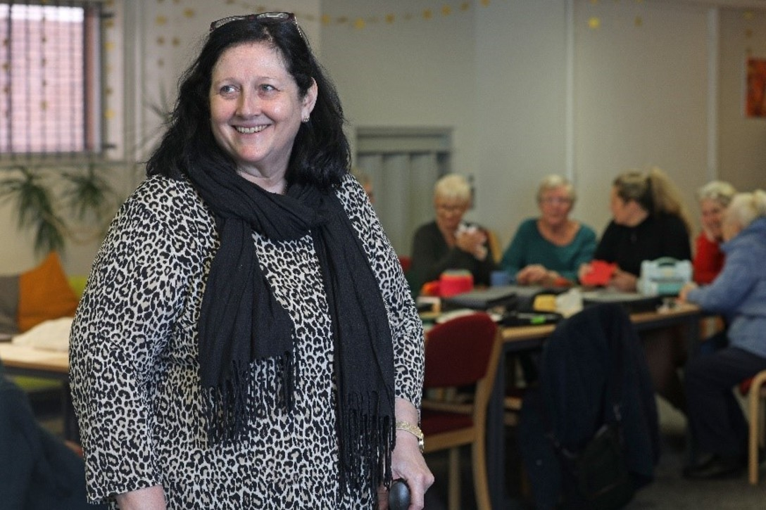 Carer smiling and looking away from the camera and elderly people in the back sitting around a table
