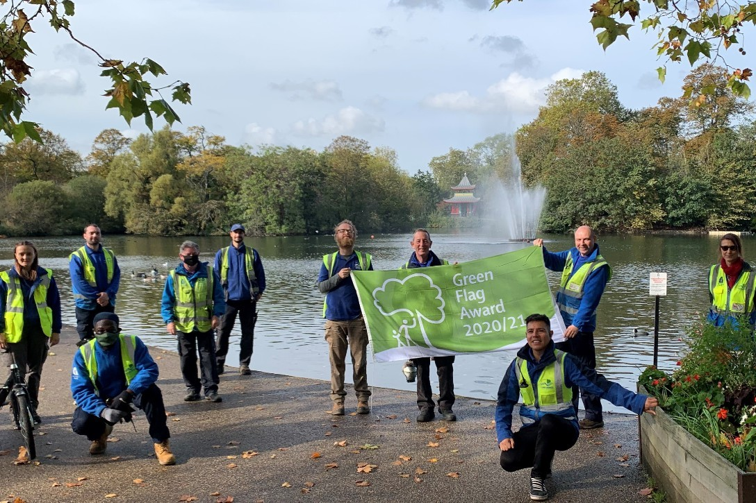 Park staff posing in front of the lake with their green flag