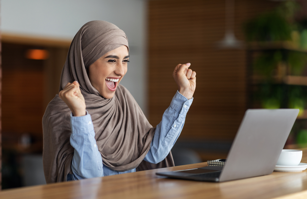 Woman smiling in front of a laptop