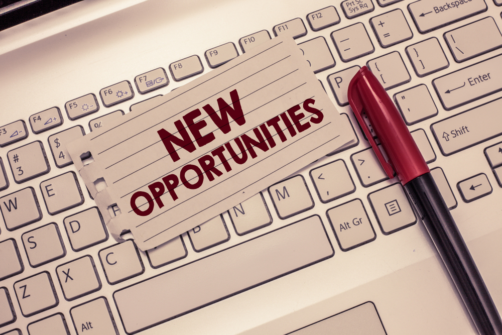 Laptop keyboard with a pen and paper on top which reads 'new opportunities'