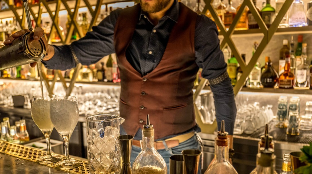 Photo of a man pouring drinks behind a bar