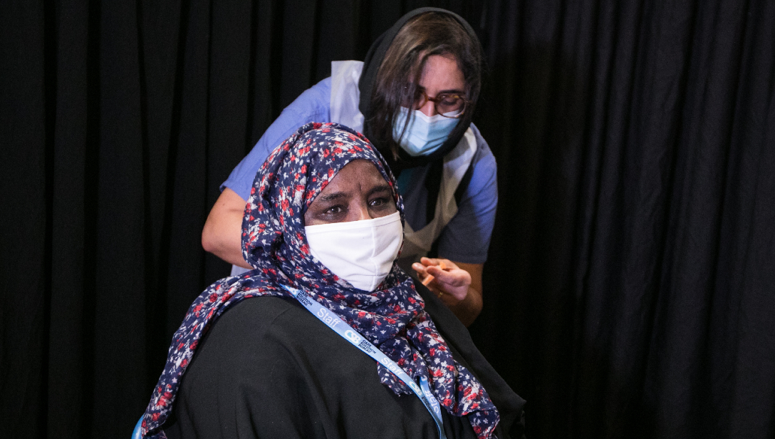 Photograph of a woman receiving a Covid-19 vaccine