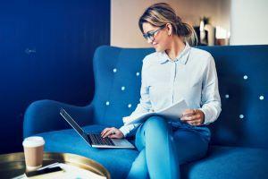 Woman sitting on blue sofa using a laptop