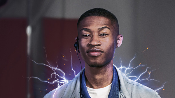 Apprentice stock image of young person smiling confidently at the camera. They have electric sparks at their shoulders.