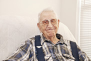 Older man sitting in chair smiling