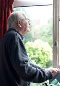 Older gentleman looking out of window