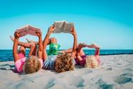 children reading on beach