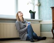 Lady sat by radiator