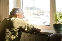Elderly gentleman looking out of window