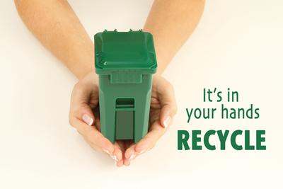 Hands holding green recycling bin