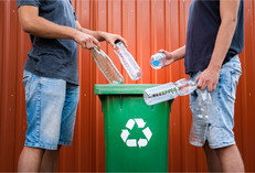 Men recycling bottles green bin