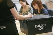 Someone putting their voting paper in a ballot box in a polling station