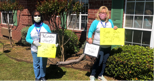 Two women wearing face masks holding signs outside a building