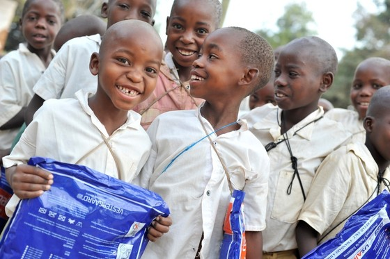 World Malaria Day 2018 banner image of school children smiling with malaria nets.