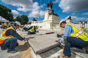 Construction Division employees resetting the large granite pavers to provide a level walking surface for visitors