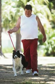 Overweight man walking dog in park