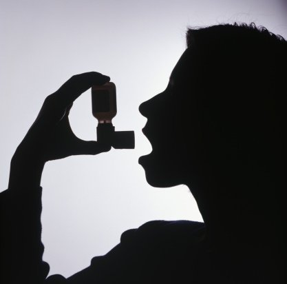 silhouette of a person using an inhaler