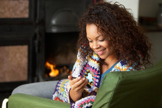 Woman looking at phone in front of fireplace