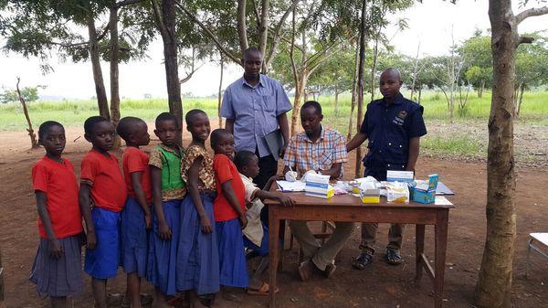 School children line up to talk to a health worker