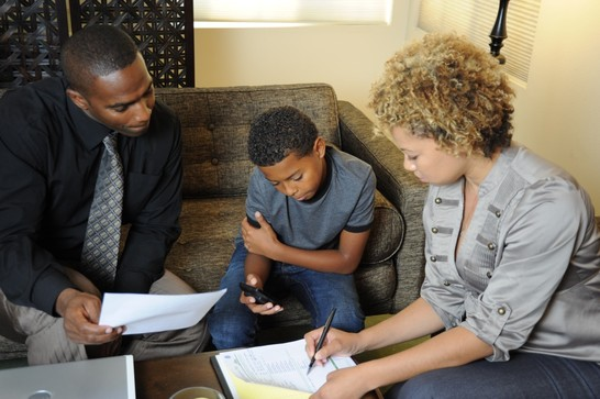 An adult man and woman and a teen boy  looking over a family communication plan