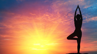 Person doing yoga pose with sunrise in background