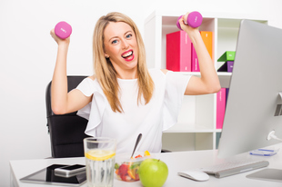Young woman holding weights at desk