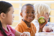 Children sitting at school lunch table, boy holding apple