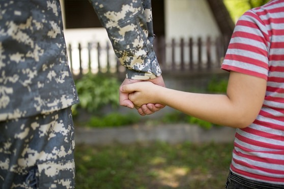 Military Service Member Holding Child's Hand