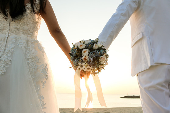 A bride and groom hold the bouquet between their hands.