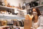 A cashier wearing a face mask wrings up a purchase at a clothing store while standing behind a plexiglass barrier at the register.