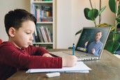 A child does math work while logged into a virtual class on his laptop.