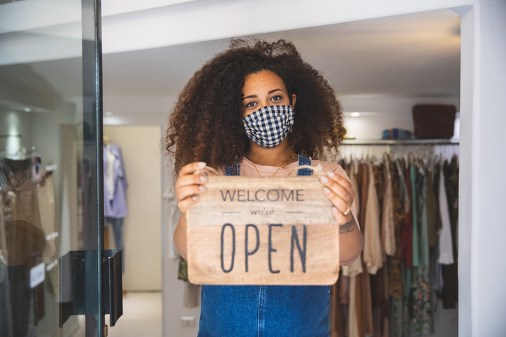 A retail worker wearing a face mask holds up a sign to indicate that her clothing store is open during the COVID-19 pandemic.