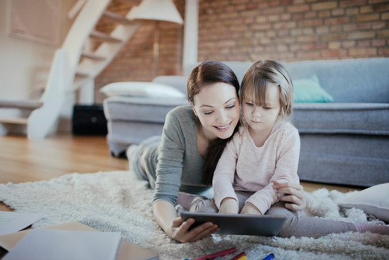 A young mother and daughter reading together on a tablet