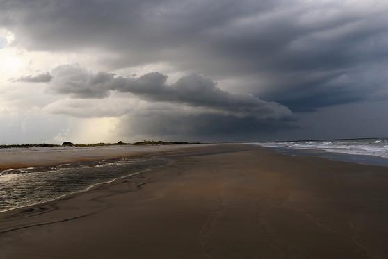 A dark cloudy sky over a beach