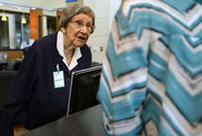 100-year-old Connie Dickinson talks with a visitor at the front desk while volunteering at Baptist Hospital. (Photo by Ryan Pelham/The Enterprise)