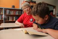 Senior Corps volunteer reads to child