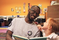 AmeriCorps member reading to young girl