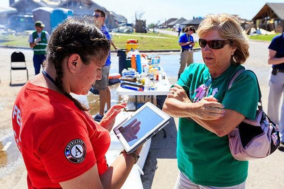 AmeriCorps FEMA Corps Brittany Bieber talks with Melanie Green after a tornado struck her neighborhood in May 2013. (Photo by Steve Zumwalt/FEMA)