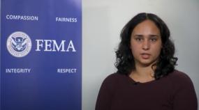 FEMA staff member sitting in front of FEMA banner