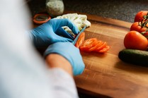 a person cutting tomatoes with protective gloves