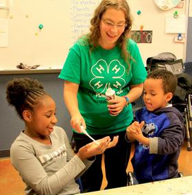 Nebraska 4-H education team member Ashley Goodman helps 4-H students