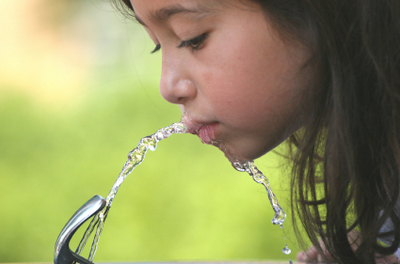 Photo: Girl drinking from water fountain