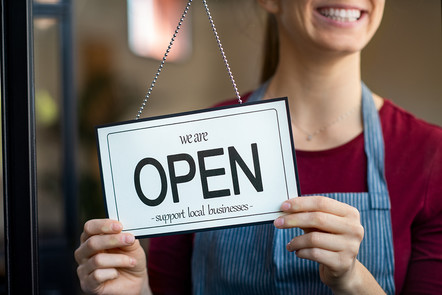 """A business owner with the sign """"We're Open - Support Local Businesses"""""""